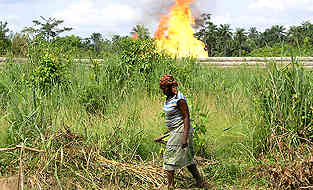 woman working near a gas flare in the Niger Delta